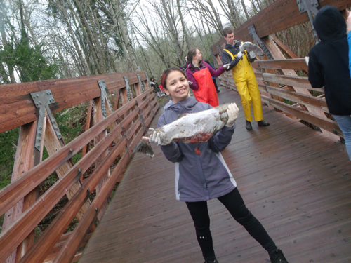 girl proudly holding salmon before she tosses it