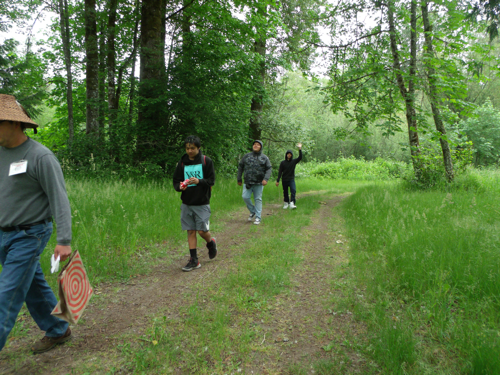 students walking down grassy trail