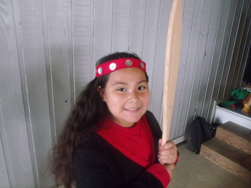 Dancer in native clothing with paddle