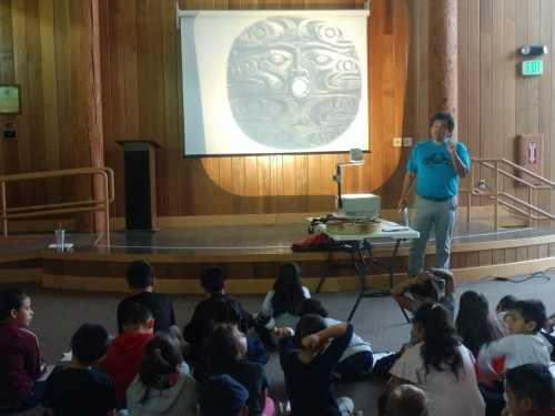 Gene Tagabon displaying art to students