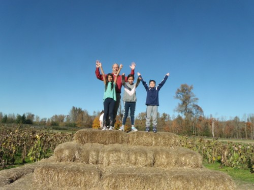 students and teacher on top of a pyramid of hay bales