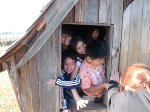 Kids crammed into a little building looking out the window