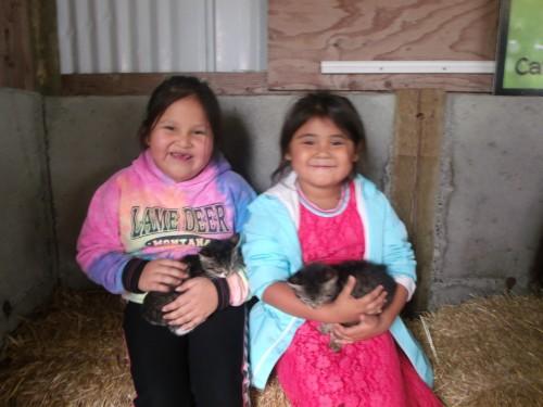 two kindergarten girls holding kittens