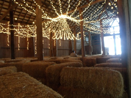 Barn decorated with bales of hay and white lights